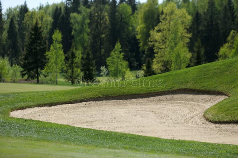 A golf course with roads, bunkers and ponds and with flag. Trees royalty free stock photography