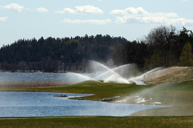 A golf course with roads, bunkers and ponds and with watering. A golf course with roads, bunkers and ponds and with flags royalty free stock photo