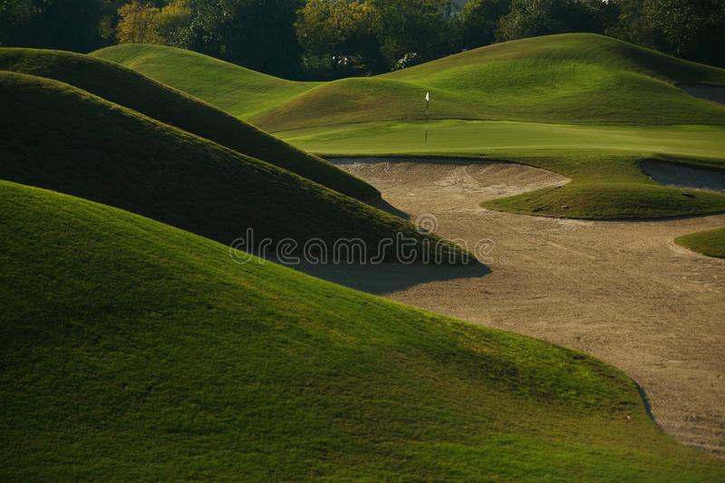 A golf course with roads, bunkers and ponds. Hills and flag in hole royalty free stock photos
