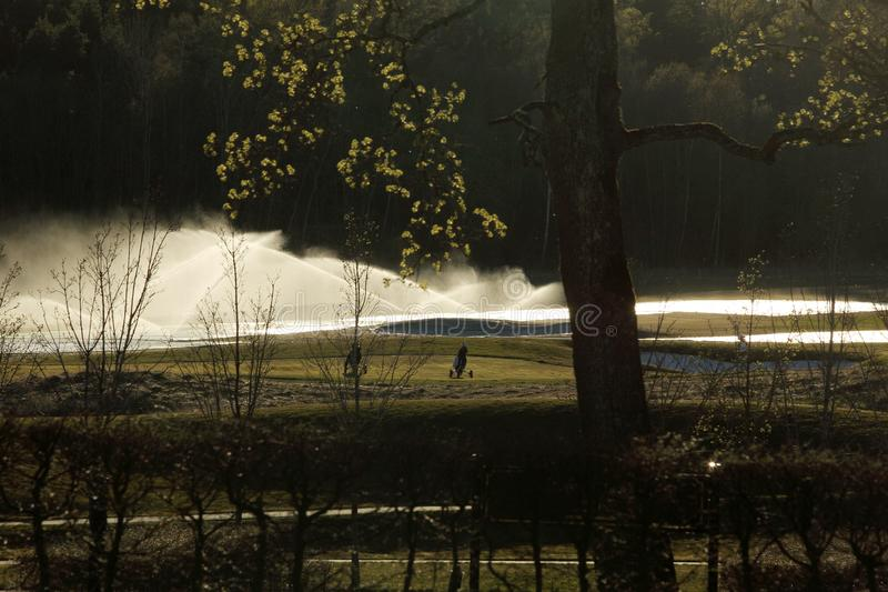 A golf course with roads, bunkers and ponds and with tree. Watering stock photography