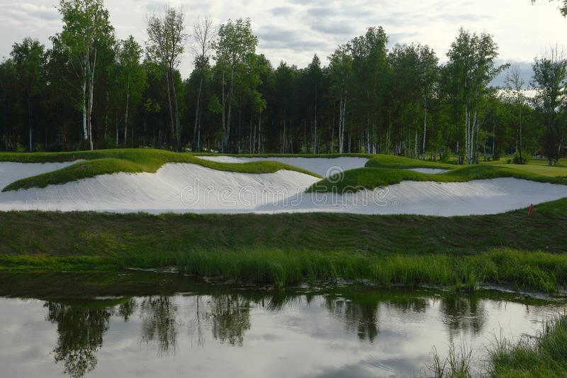 A golf course with roads, bunkers and ponds. And trees royalty free stock image