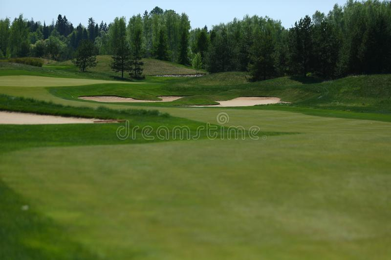 A golf course with roads, bunkers and ponds and with watering stock photography