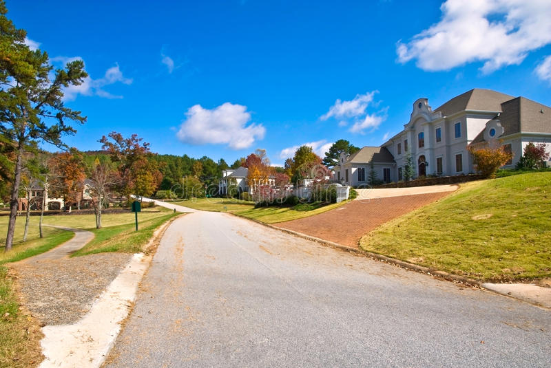 Golf Course Subdivision/Homes. Large houses on a street in a golf course community with the cart path coming into the road on the left royalty free stock images