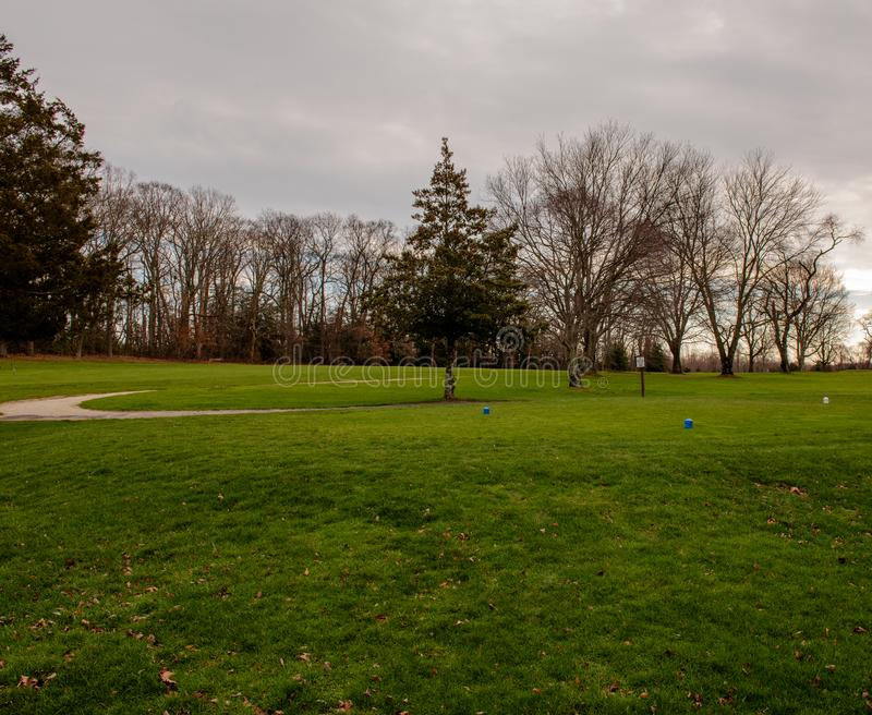A Golf Course Tee Box. Uphill photo of a golf course tee box on a cloudy winter day stock images