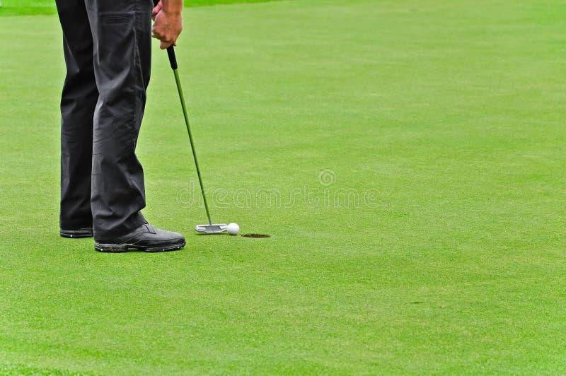 Golf, dat in gat de bal zet stock afbeeldingen