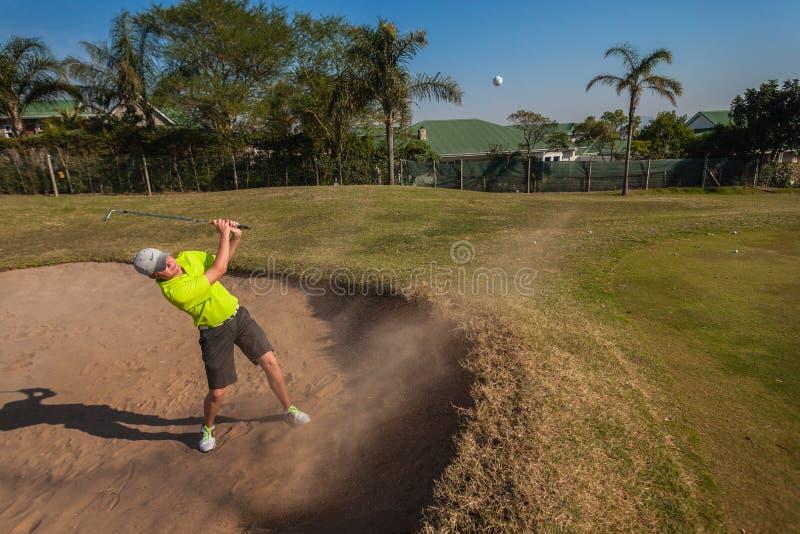 Golf de pratique en matière de boule de tir de sable de joueur image stock