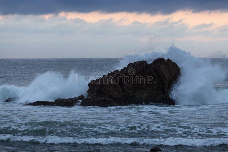 Golf die tegen een Rots in de Vreedzame Oceaan verpletteren stock foto's