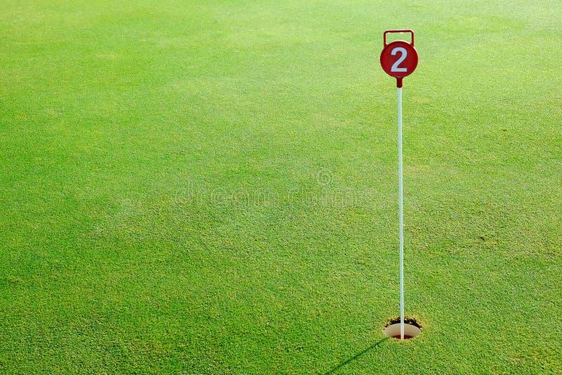 Golf el agujero del putting green de la práctica y marcado con una muestra roja fotografía de archivo libre de regalías