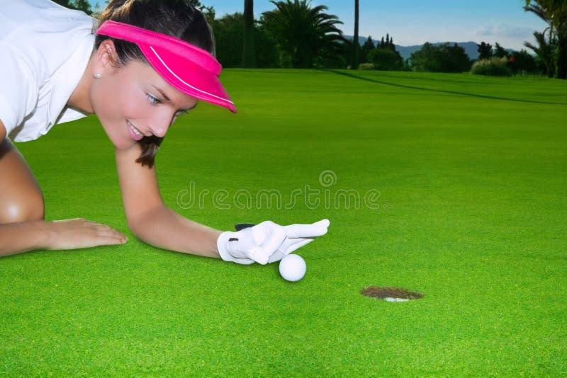 Golf el humor verde de la mujer del agujero que chasquea la mano una bola imagenes de archivo
