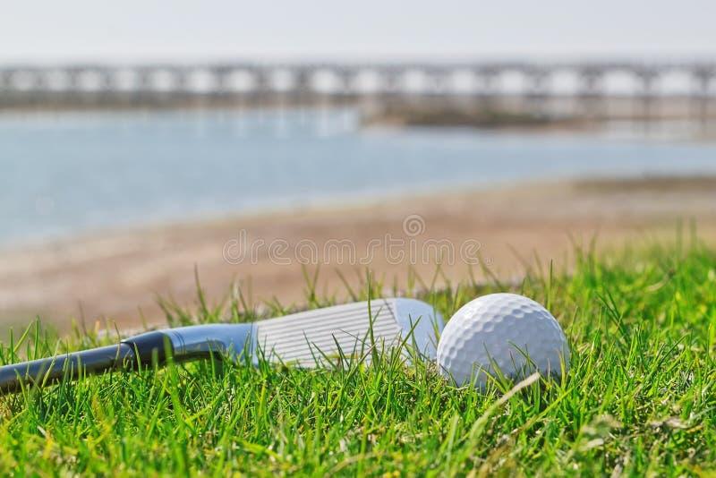 Golf el palillo y la bola en hierba con un fondo de la naturaleza. imagenes de archivo