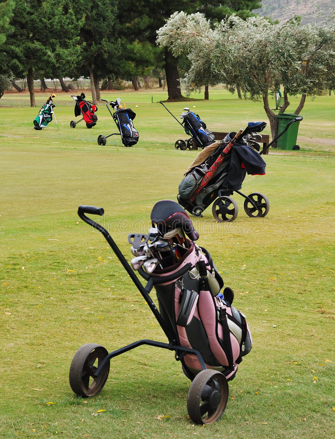 Golf equipment. Group of six golf bags with equipment on green playing field royalty free stock image