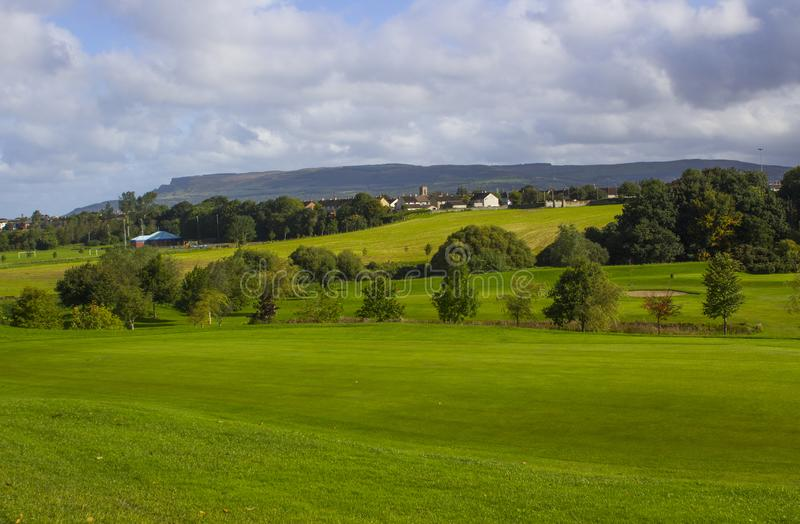 A golf fairway and green in the parkland course in the Roe river valley near Limavady in Northern Ireland. With the magnificent Bienevenagh Mountain in the royalty free stock photography