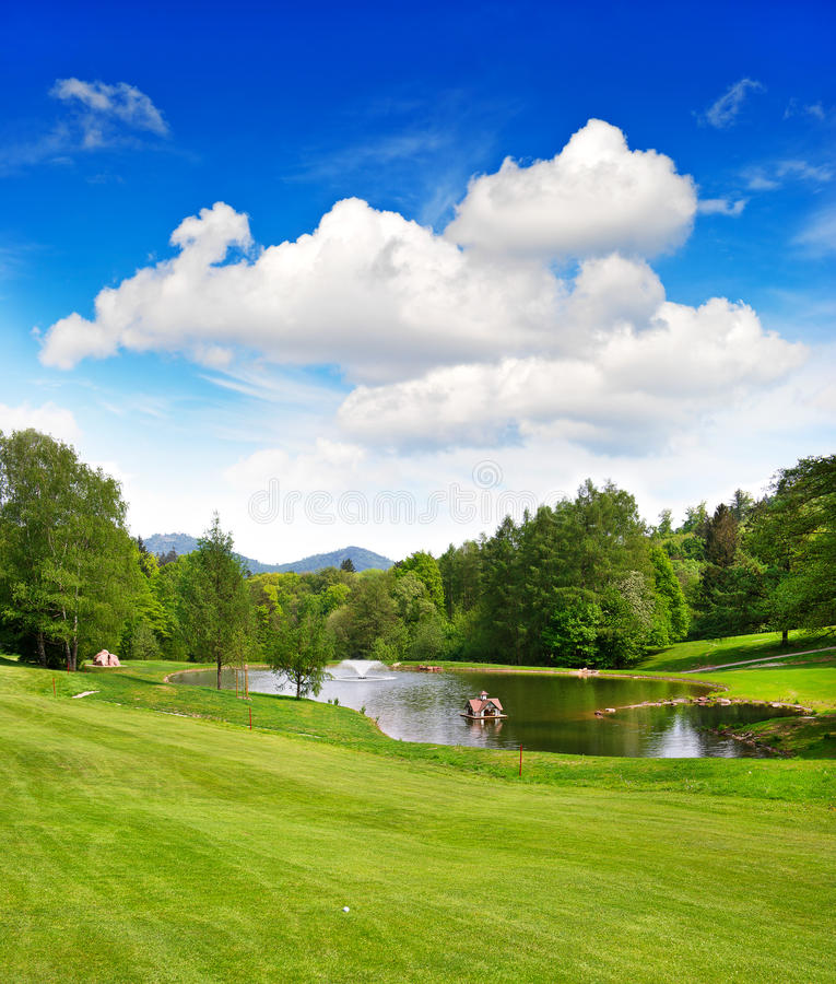 Golf field with beautiful blue sky and lake. European landscape stock photo