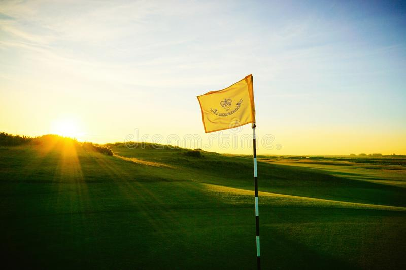 Golf course flag early morning. Golf course flag lit up and waving in the breeze as the suns rays begin to shine over the dunes stock images