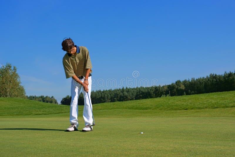 Golf golfare som tränger bollen in i hålet royaltyfri foto