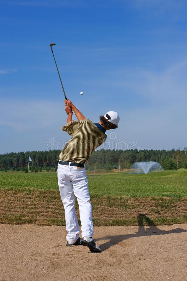 Golf, golfer striking the ball from the bunker royalty free stock photo