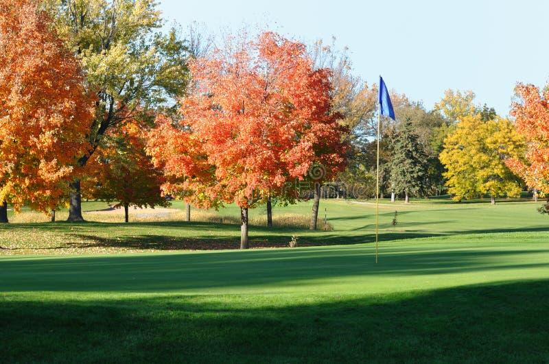 Golf Grün und Flagstick mit bunten Fall-Blättern stockbild