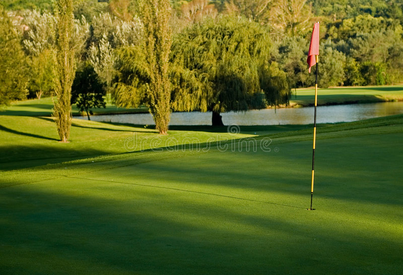 Golf green, flag and water hazard stock images