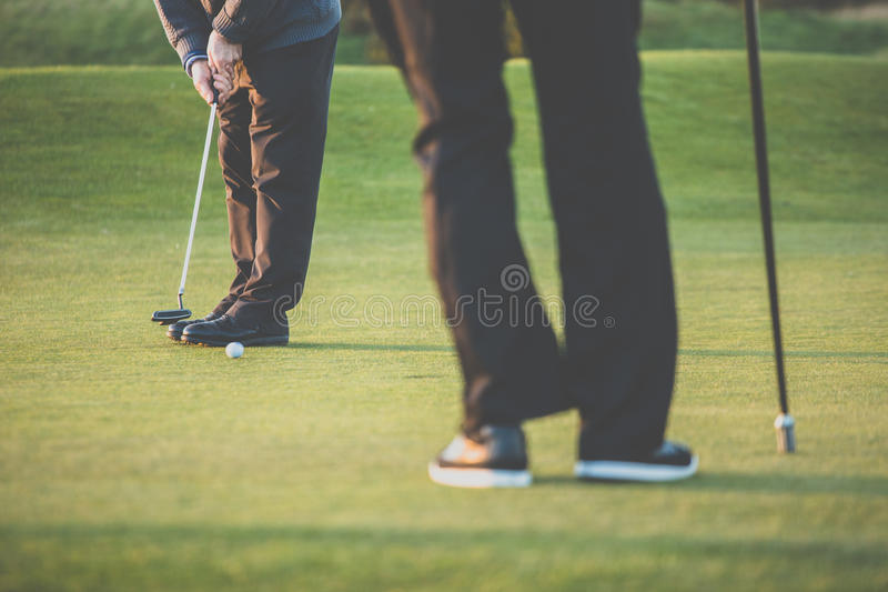 Golf green sceen - golfer putting near the hole, short putt. (colort toned image with reduced contrast and some added noise royalty free stock photo