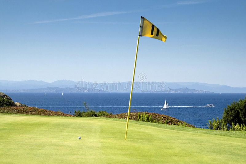 Golf green by the sea. Photography of a golf green with a golf ball next to the hole with a yellow flag (hole number 11) and mediterranean sea in the background stock photo