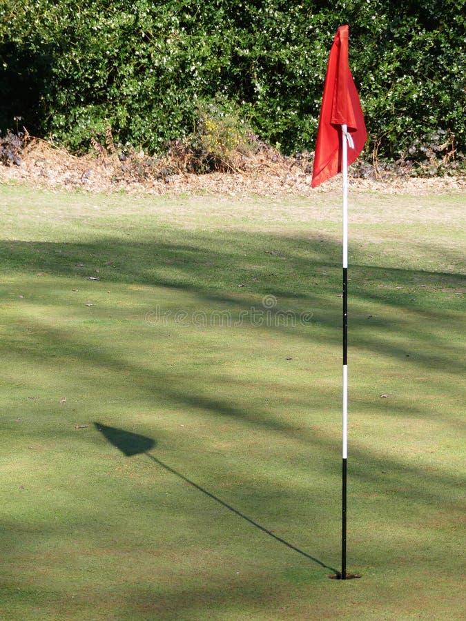 Golf groen met rode vlag gietende schaduw stock foto's