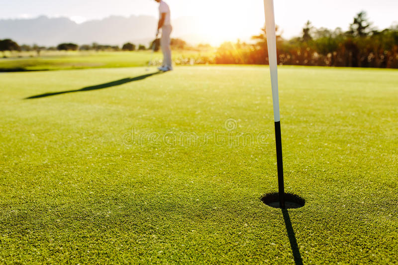 Golf hole and flag in the green field stock photos