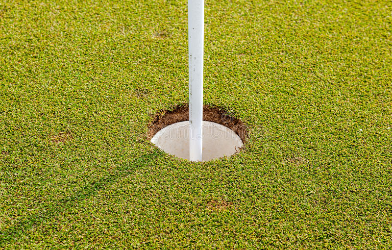 The golf hole and flag on green grass of golf course in Thailand royalty free stock photography