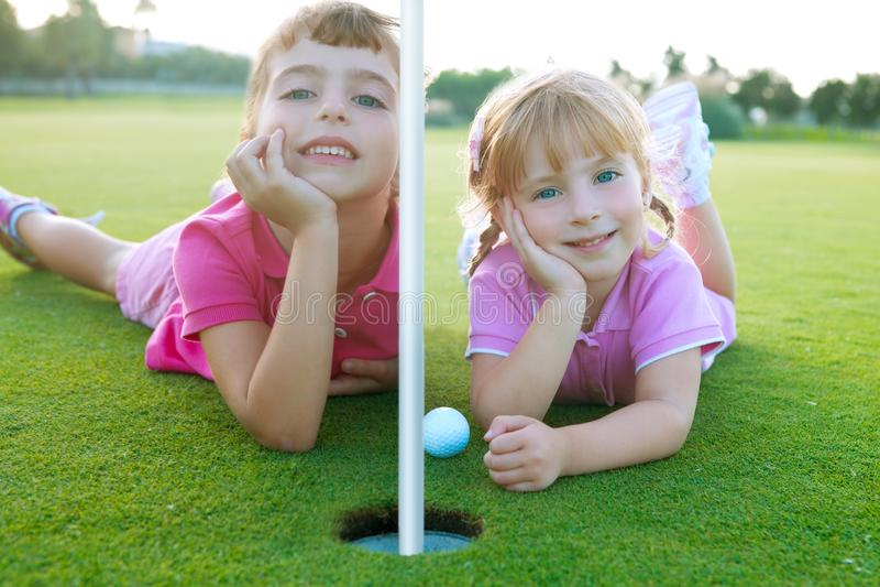 Golf a las muchachas de la hermana relajadas poniendo la bola verde del agujero fotografía de archivo