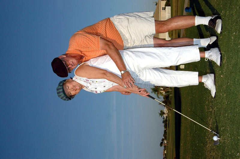 Golf lesson. A senior man gives a golf lesson to his partner at the tee off (his hands reaching around her to assit her with her grip on club