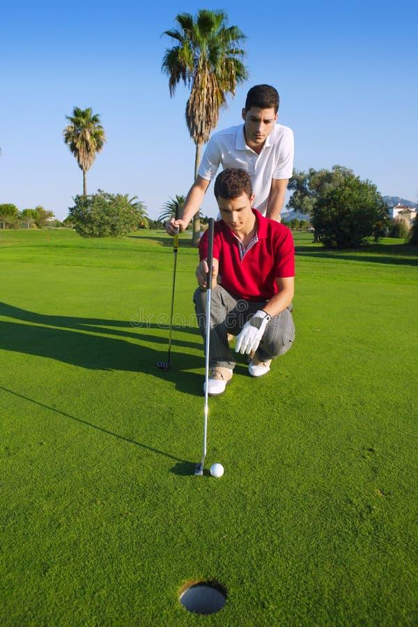 Golf o homem novo que olha e que aponta o furo foto de stock