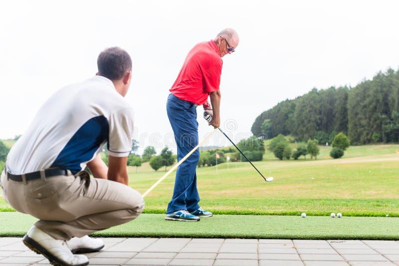 Golf o instrutor que trabalha com o jogador de golfe no driving range imagem de stock