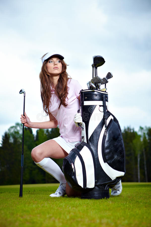 Golf player. Portrait of a woman holding a golf club in her hands on a green stock photography