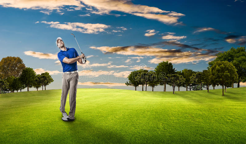 Golf Player. In a blue shirt taking a swing, on a golf course royalty free stock photos