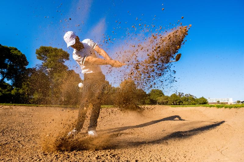 Golf player hits the ball from the bunker and splashes sand stock photos