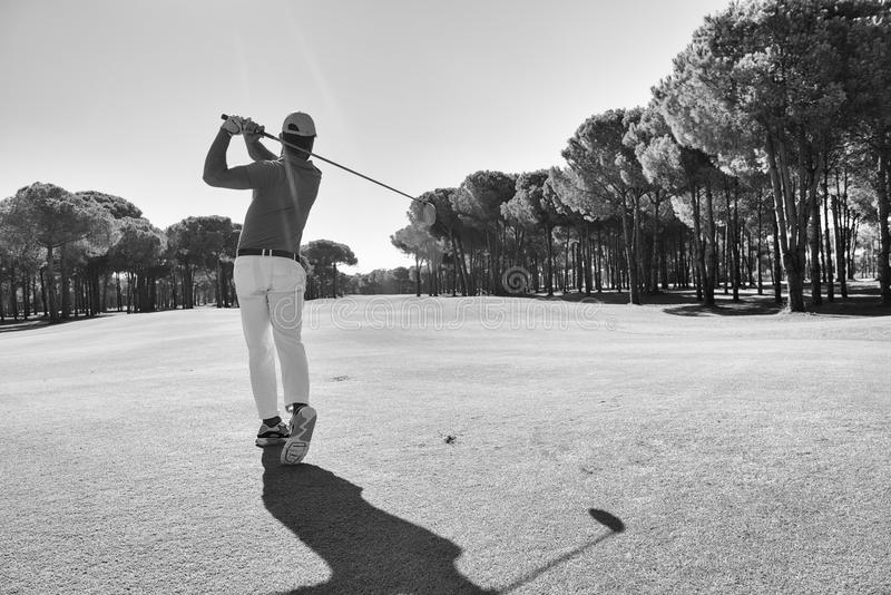 Golf player hitting shot with club stock images