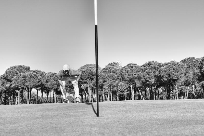 Golf player hitting shot with club on course stock image