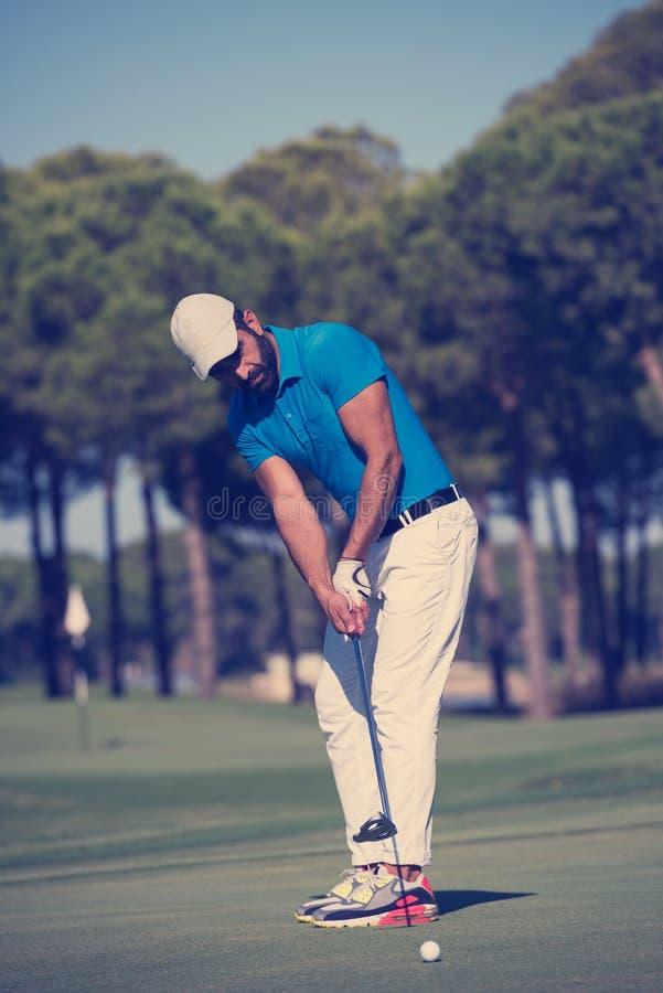 Golf player hitting shot at sunny day stock photo