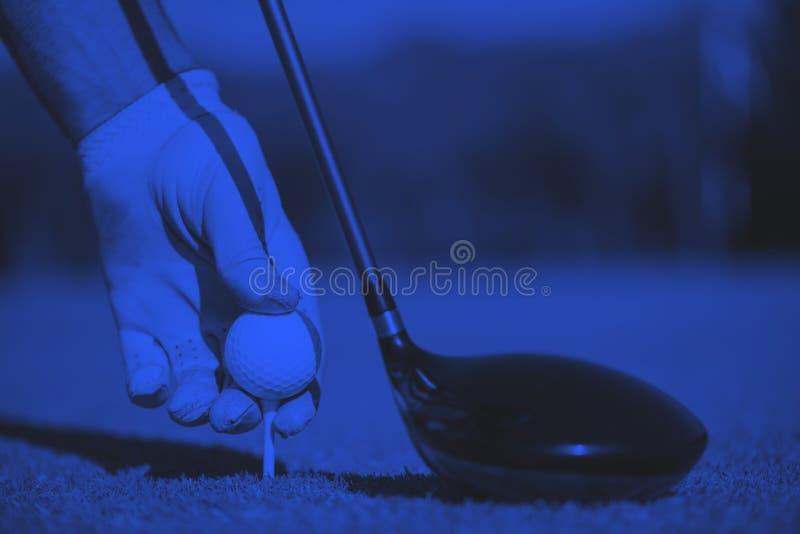 Golf player placing ball on tee stock photos