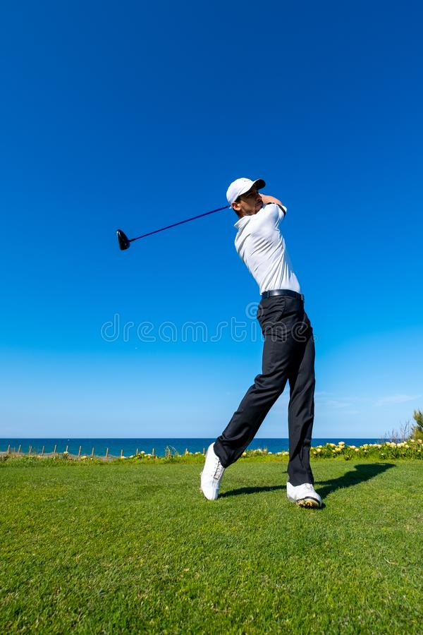 Golf player plays on a golf course royalty free stock image