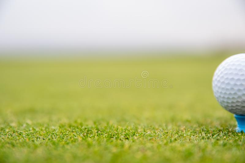 A golf player prepares the ball to be fired at the golf course royalty free stock photo
