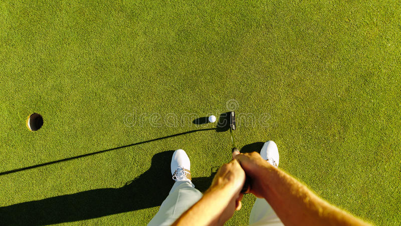 Golf player at the putting green hitting ball into a hole royalty free stock images