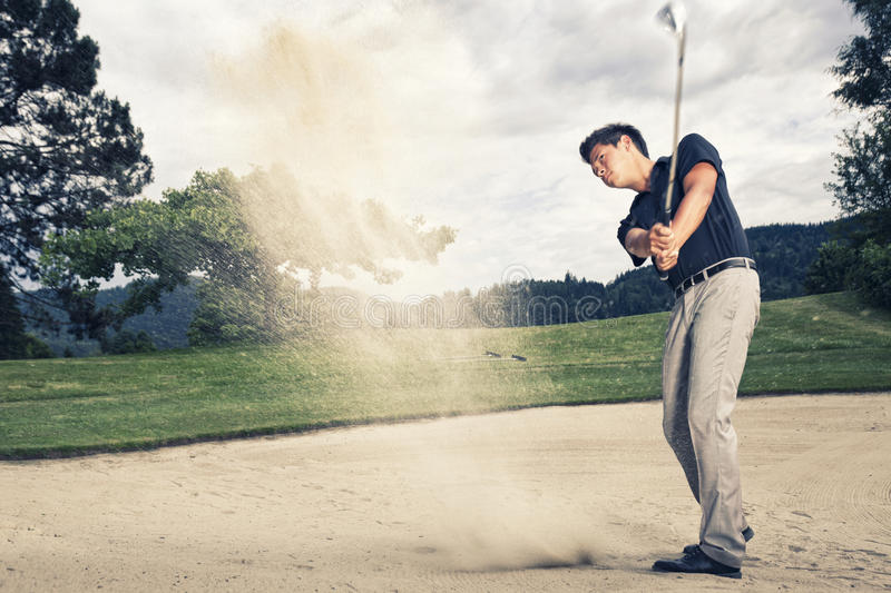 Golf player in sand trap. Male golfer in blue shirt and grey pants hitting golf ball out of a sand trap with sand wedge and sand caught in motion stock photos