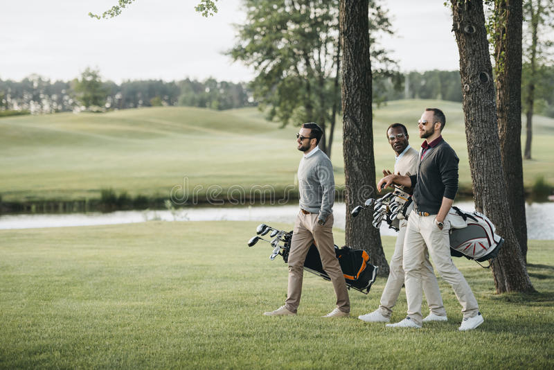 Golf players holding bags with golf clubs and walking on golf course royalty free stock image