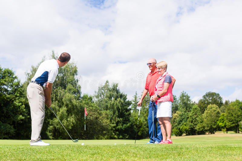 Golf pro practicing the sport with senior woman and man. Golf pro practicing the sport with senior women and man royalty free stock images