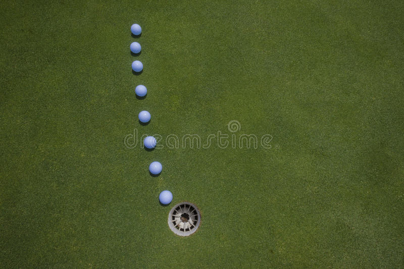 Golf Putt Balls Hole. Golf putting balls lined up on a visionary line to the hole on a well manicured golf course green royalty free stock images