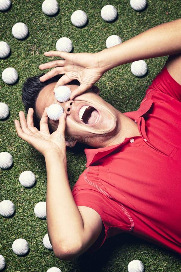 Golf spelare på golv med bollar på ögon. royaltyfri foto