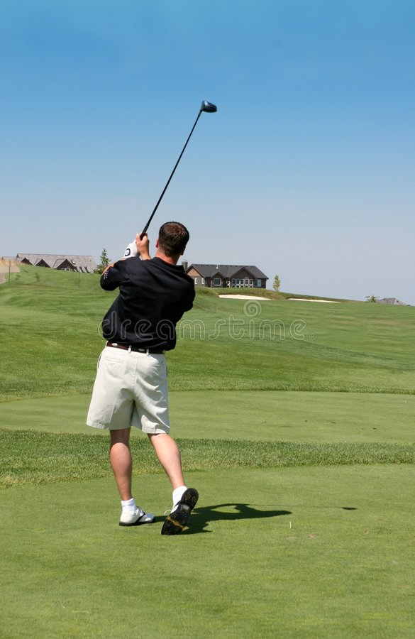 Golf Swing. A man watching where his ball went after he swung stock photo