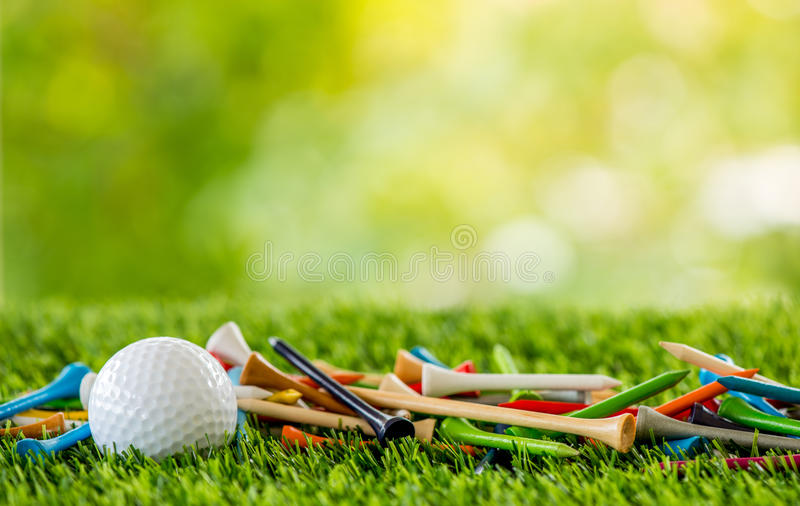 Golf tees with ball. On green field stock photography