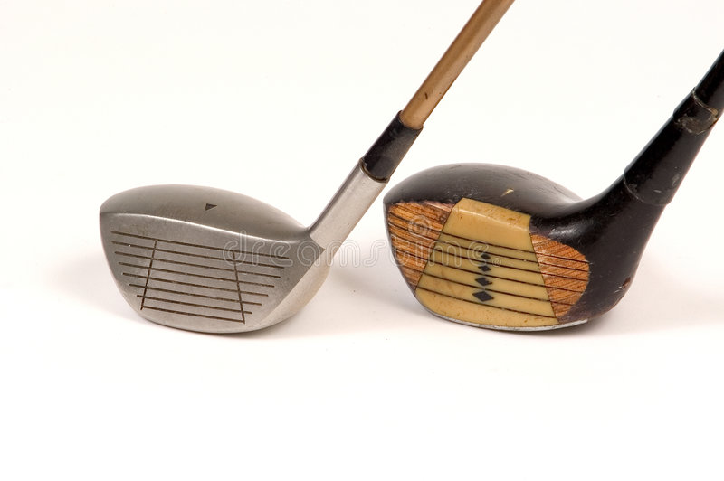 Golf Tools. Antique wooden laminated driver beside steel driver with graphite shaft stock photo