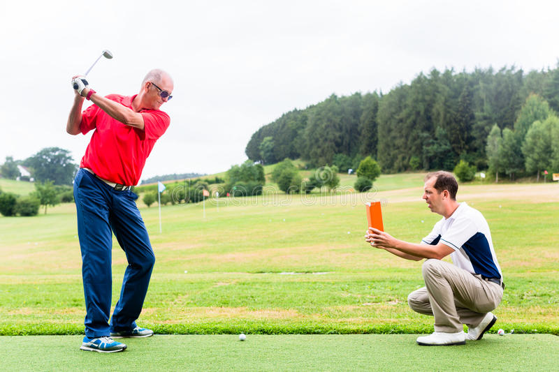 Golf trainer recording video of senior golf player stock photography